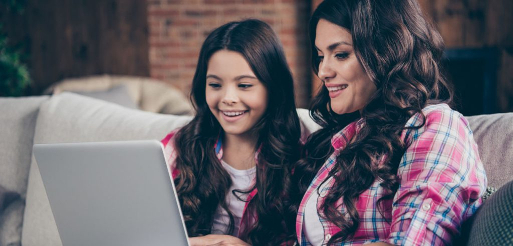 Image of a mother and daughter looking at a screen.